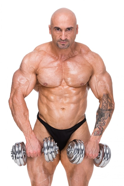 Muscular bodybuilder exercising with two weights. Premium Photo