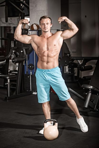 ジムで体重と演習を行う筋肉ボディービルダー男 無料写真