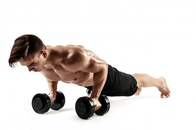 Muscular bodybuilder guy doing push-ups on dumbbells from the floor over white background Premium Photo