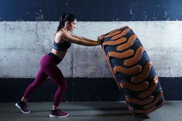 Donna di corporatura muscolare che lavora in palestra lanciando pneumatici per camion Foto Gratuite