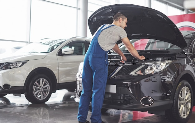 Muscular car service worker repairing vehicle. Free Photo