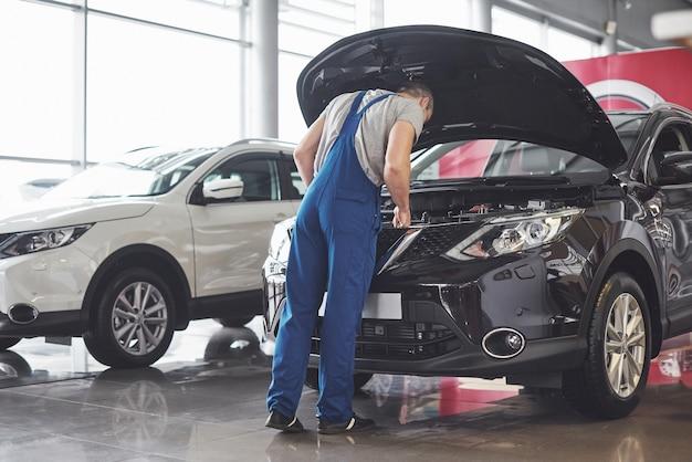 Muscular car service worker repairing vehicle. Free Photo