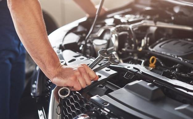 Lavoratore di servizio auto muscolare che ripara veicolo. Foto Gratuite
