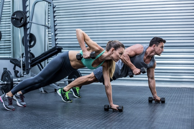 Muscular couple doing plank exercise together Premium Photo