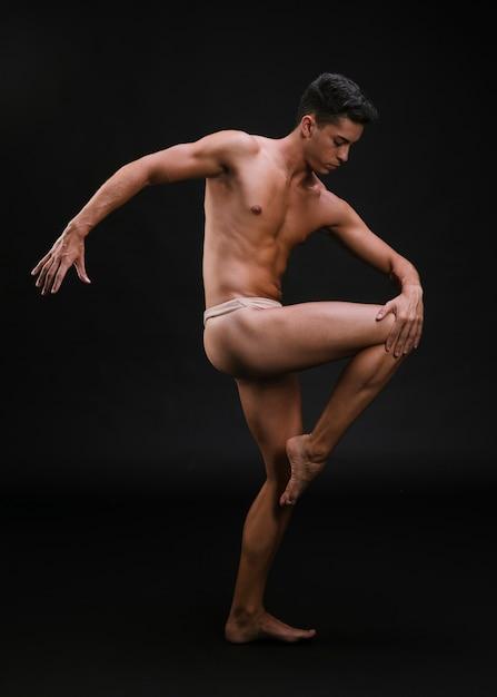 Muscular dancer stretching leg Free Photo