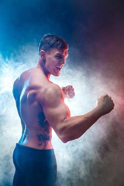 Muscular  fighter punching in smoke. colour background. Premium Photo