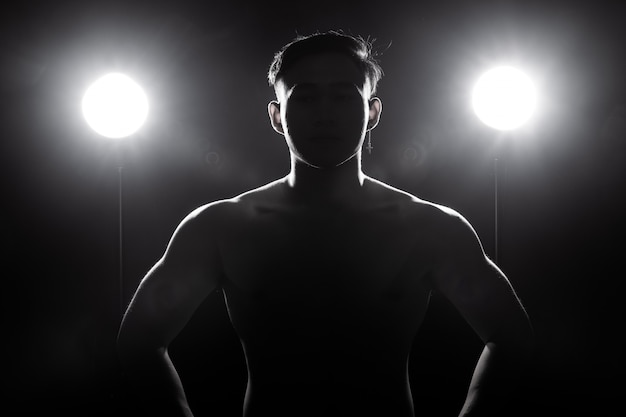Muscular Fitness Man Exercises Healthy Lifestyle In Dark Background Silhouette Back Light Premium Photo