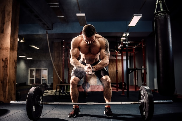 Muscular fitness man preparing to deadlift a barbell over his head in modern fitness center.functional training. Premium Photo