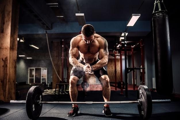 モダンなフィットネスセンターで彼の頭の上にバーベルをデッドリフトする準備をして筋肉のフィットネス男。 Premium写真