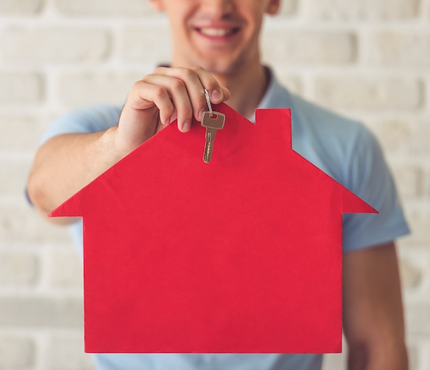 Muscular guy in blue t-shirt holding a paper house Premium Photo