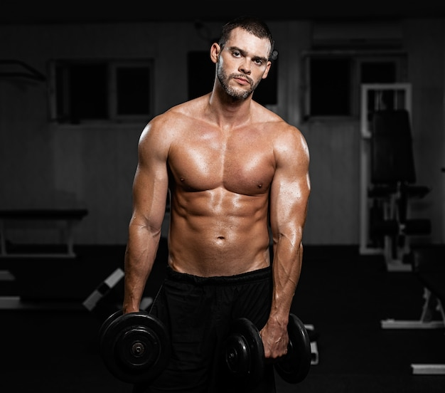 Muscular male athlete posing with dumbbells in the gym Premium Photo