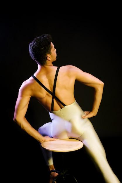Muscular male ballet dancer sitting in spotlight Free Photo