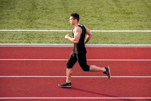Muscular male runner running on red race track Free Photo