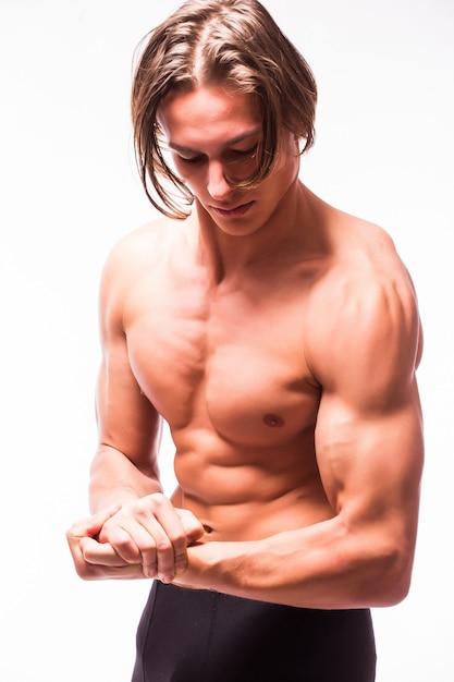 Мускулистое мужское тело с шестью пакетами, изолированное на белой стене Бесплатные Фотографии