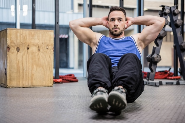 Muscular man doing abdominal crunches at the crossfit gym Premium Photo