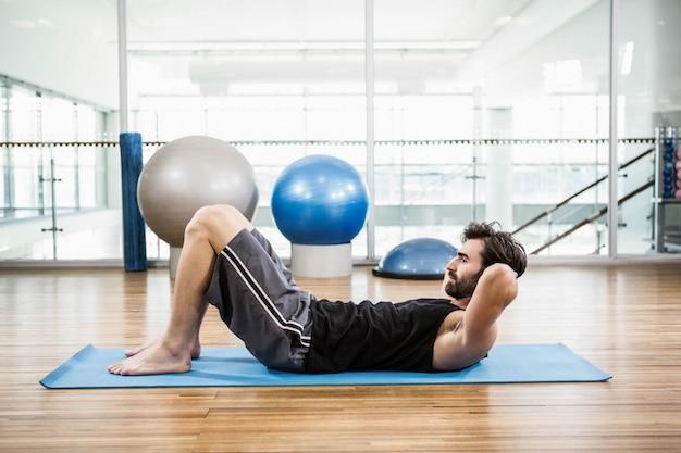 Muscular man doing abdominal on mat in the studio Premium Photo