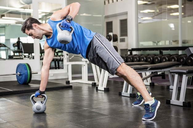 Muscular man doing exercises with kettlebells at the gym Premium Photo