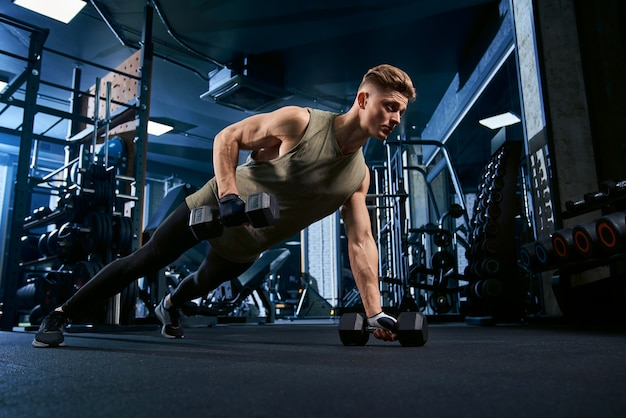 Muscular man doing push ups on one hand. Free Photo