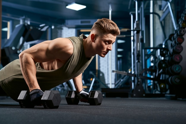 Muscular man doing push ups using dumbbells. Free Photo