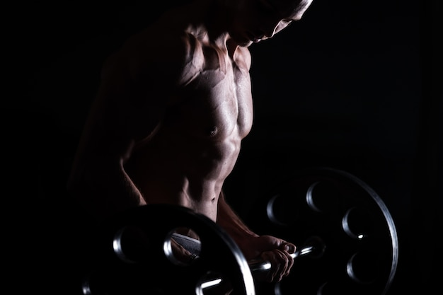 Muscular man doing weight lifting in fitness center Free Photo