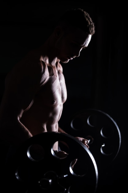 Muscular man doing weightlifting in fitness center Free Photo