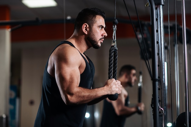 Muscular man during a workout at the gym trains the triceps Premium Photo