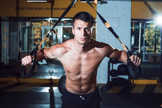 Muscular man exercising with fitness strap in gym Free Photo