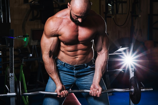 Muscular man lifting barbell Free Photo