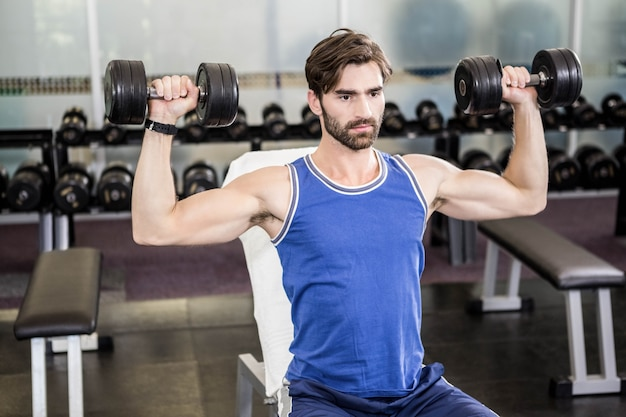 Muscular man lifting dumbbells on bench at the gym Premium Photo