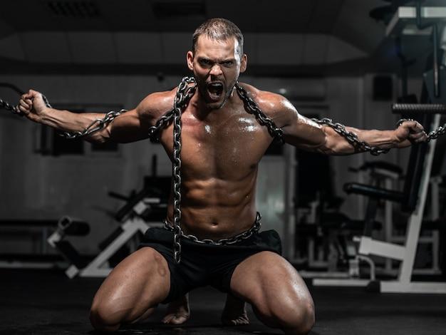 Muscular man slave in chains in gym, the prisoner Premium Photo