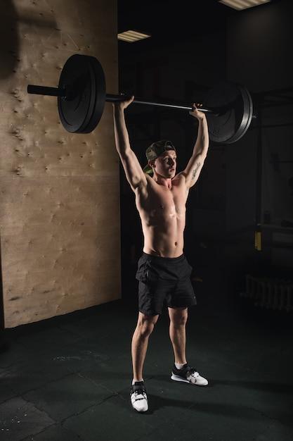 ジムで頭の上にバーベルを発生させてひげ列車と筋肉の男 Premium写真