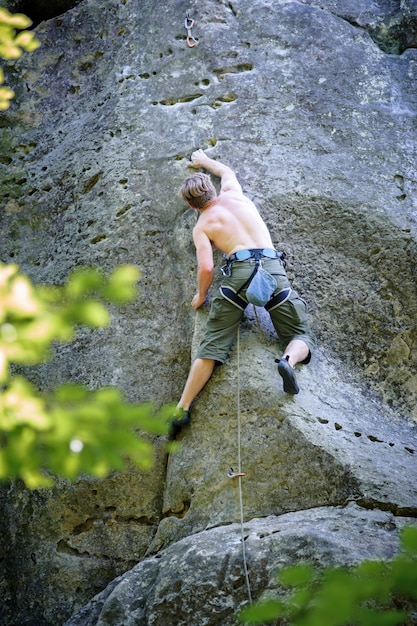 Muscular rock climber climbs on cliff wall with rope Premium Photo