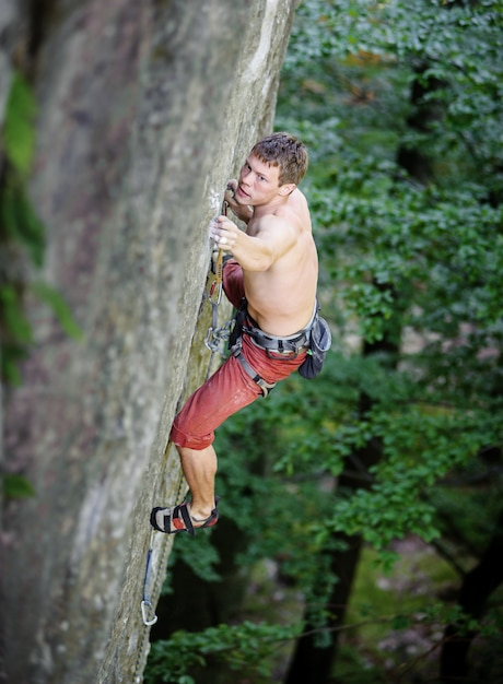 Muscular rock climber climbs on overhanging cliff in summer time Premium Photo