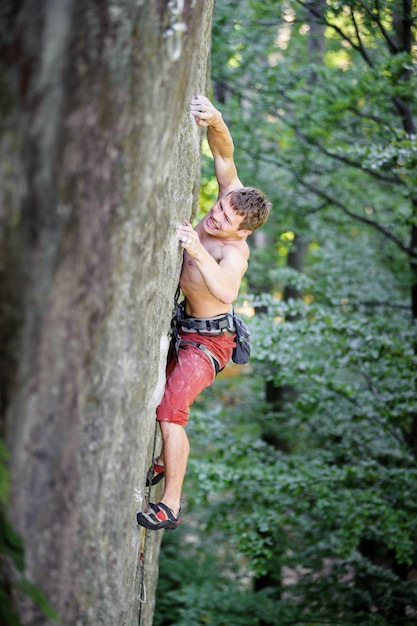 Muscular rock climber climbs on overhanging cliff Premium Photo