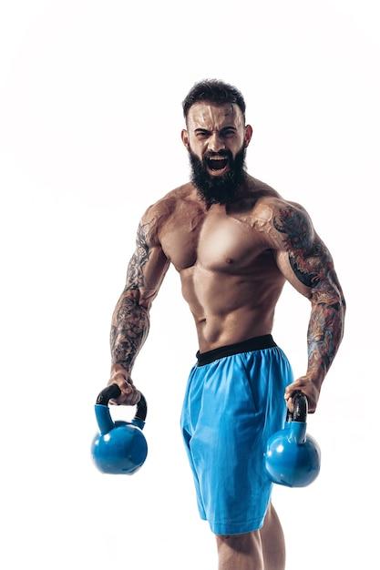 ケトルベルと筋肉の上半身裸の入れ墨をしたひげを生やした男性アスリートボディービルダートレーニング Premium写真