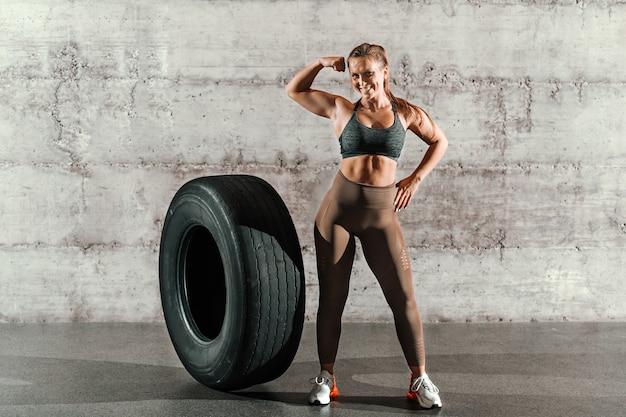 ポニーテールとジムで灰色の壁の前に大きなタイヤの横にポーズをとってスポーツウェアで筋肉の笑顔ブルネット。 Premium写真