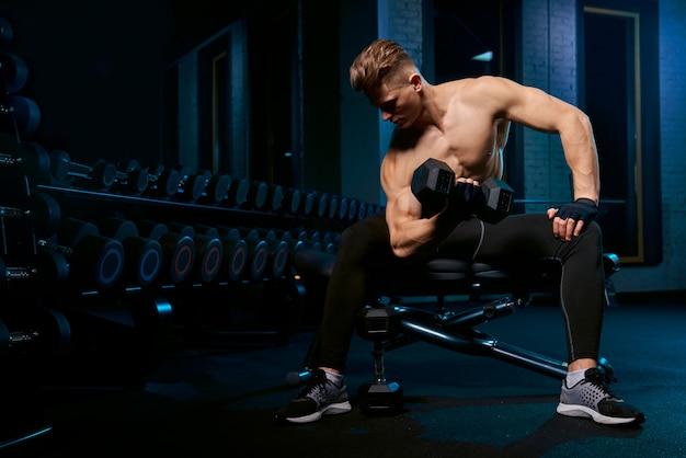 ダンベルで上腕二頭筋を構築する筋肉のスポーツマン。 無料写真