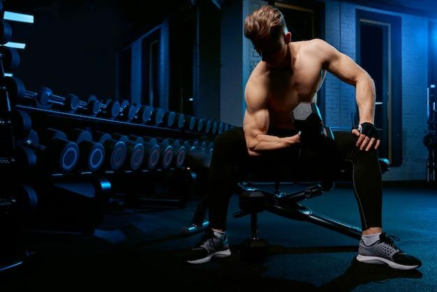 Мускулистый спортсмен тренировки руки с гантелями. Бесплатные Фотографии