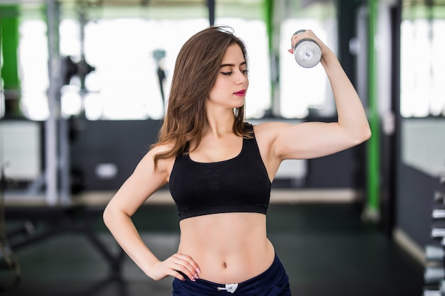 Muscular woman working out in fitness centre with two dumbbells Free Photo