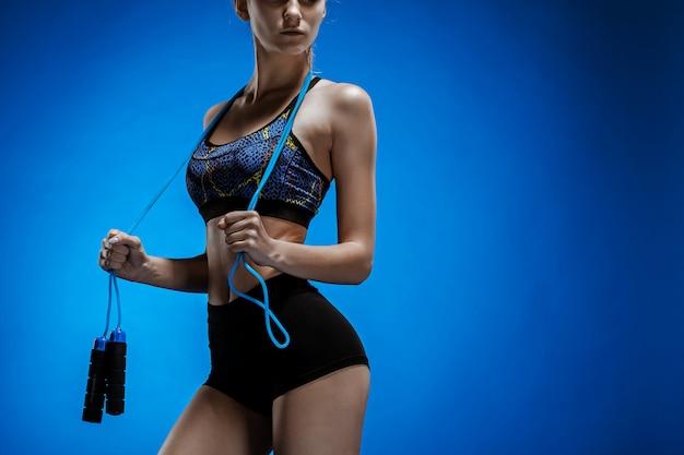Giovane atleta muscolare con una corda per saltare sul blu Foto Gratuite
