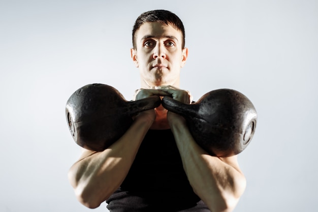 Muscular young man doing heavy weight exercise for biceps. Premium Photo