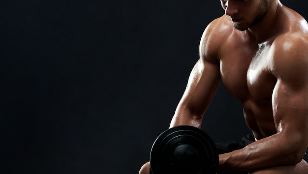 Muscular young man lifting weights on black background Free Photo