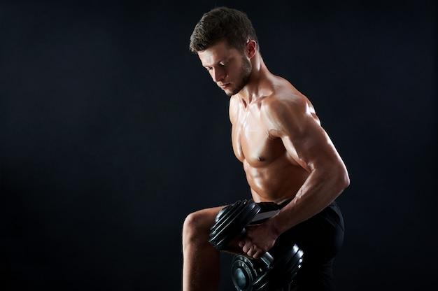 黒の背景にウェイトを持ち上げる筋肉の若い男 無料写真
