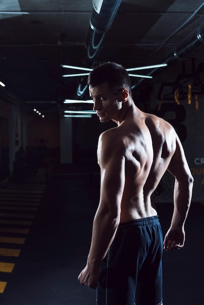 Muscular young man standing in gym Free Photo
