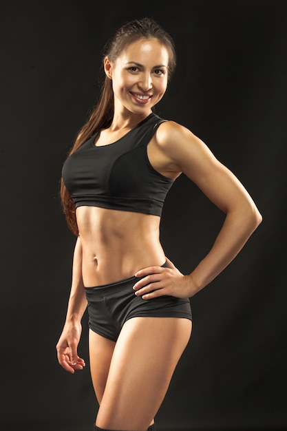 Muscular young woman athlete on black Free Photo