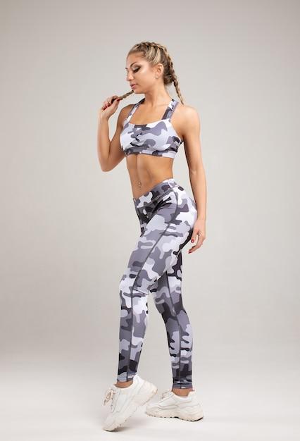 灰色の筋肉の若い女性の運動選手。 Premium写真