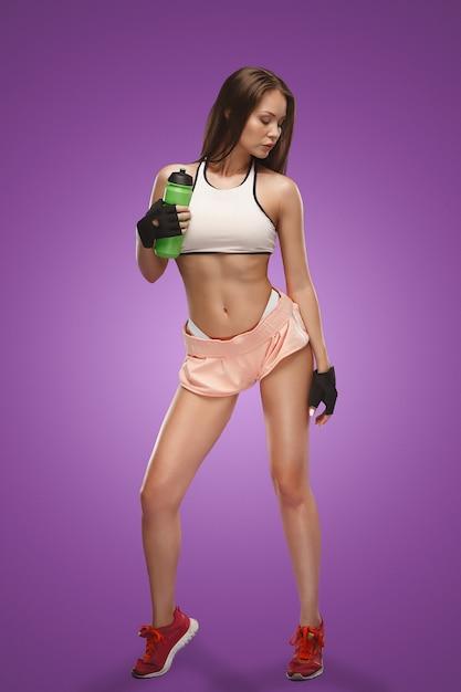 水を飲むとライラックのスタジオでポーズ筋肉の若い女性アスリート 無料写真