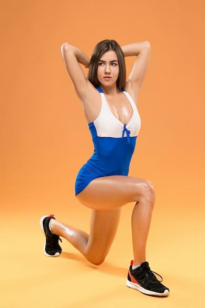 オレンジ色の背景のスタジオでポーズ筋肉の若い女性アスリート 無料写真