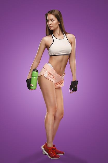 スタジオでポーズ筋肉の若い女性アスリート 無料写真