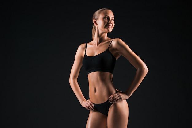 黒でポーズ筋肉の若い女性アスリート 無料写真